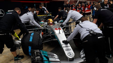 Mechanics push the car of Mercedes driver Lewis Hamilton of Britain during a Formula One pre-season testing session at the Catalunya racetrack in Montmelo, outside Barcelona, Spain, Tuesday, Feb. 28, 2017. (AP Photo/Francisco Seco)