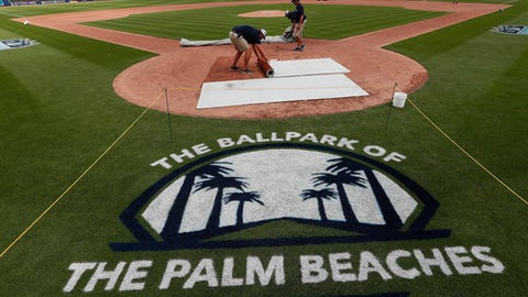 Grounds crew members work to ready the field at The Ballpark of the Palm Beaches before a spring training baseball game between Houston Astros and Washington Nationals Tuesday, Feb. 28, 2017, in Palm Beach, Fla. The new stadium will be the spring training home for both the Astros and Nationals. (AP Photo/John Bazemore)