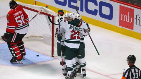 Jan 15, 2017; Chicago, IL, USA; Minnesota Wild right wing Jason Pominville (hidden) celebrates scoring a goal with teammates while Chicago Blackhawks goalie Corey Crawford (50) reacts during the third period at the United Center. Minnesota won 3-2. Mandatory Credit: Dennis Wierzbicki-USA TODAY Sports