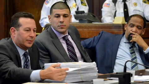 Former New England Patriots football player Aaron Hernandez, center, and defense attorney Ronald Sullivan watch as lead attorney Jose Baez presents a stack of discovery documents as the reason for requesting a continuance in Hernandez' upcoming double murder trial. (Chris Christo /The Boston Herald via AP, Pool)
