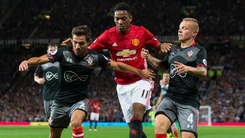 Manchester United's Anthony Martial, centre, fights for the ball against Southampton's Cedric Soares, left, and Jordy Clasie during the English Premier League soccer match between Manchester United and Southampton at Old Trafford Stadium, Manchester, England, Friday, Aug. 19, 2016. (AP Photo/Jon Super)