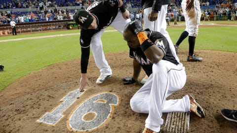 Miami Marlins' Marcell Ozuna, right, sits on the pitcher's mound with the number 16 in honor of Marlins pitcher Jose Fernandez, after a baseball game against the New York Mets, Wednesday, Sept. 28, 2016, in Miami. Fernandez was killed in a boating accident in Miami Sunday. The Mets defeated the Marlins 5-2. (AP Photo/Lynne Sladky)