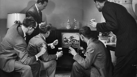 circa 1955:  A group of five men sit around a television set, watching a football game and holding glasses of beer in a living room.  (Photo by Lambert/Getty Images)