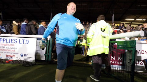 Sutton reserve goalkeeper Wayne Shaw walks near the playing area before the FA Cup 5th round soccer match at Gander Green Lane, Sutton, London, Monday Feb. 20, 2017. A  backup goalkeeper paid the price for eating a meat pie during his team's landmark game against Arsenal, resigning from Sutton United as authorities launched investigations into the apparent betting stunt. A British newspaper's betting company, which sponsored Sutton United for Monday's FA Cup game, had 8-1 odds that overweight reserve goalkeeper Wayne Shaw would eat a meat pie. (Andrew Matthews/PA via AP)