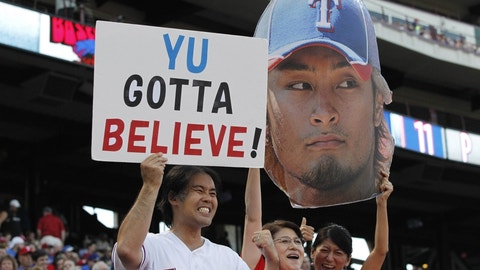 Sep 24, 2013; Arlington, TX, USA; Texas Rangers fans hold up a sign and a likeness of Texas Rangers starting pitcher Yu Darvish (11) before the game against the Houston Astros at Rangers Ballpark in Arlington. Mandatory Credit: Tim Heitman-USA TODAY Sports