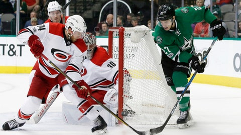 Dallas Stars' Adam Cracknell (27) attacks the net before scoring as Carolina Hurricanes' Jaccob Slavin (74) and goalie Cam Ward defend  during the third period of an NHL hockey game, Saturday, Feb. 11, 2017, in Dallas. (AP Photo/Mike Stone)