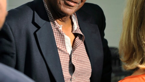 FILE - In this May 29, 2013, file photo. former Cleveland Browns wide receiver Reggie Rucker chats after a news conference for Hall of Fame running back Jim Brown in Cleveland. Federal prosecutors say Rucker owes more than $110,000 for stealing from two charities, and they want to garnish his earnings from the NFL for restitution. Cleveland.com reports that could include his pension and any money he might receive from a nearly $1 billion class-action settlement that the NFL agreed to pay to athletes who suffered concussions. Players have months to submit claims in that settlement. Rucker's attorney says the imprisoned 69-year-old intends to use settlement money as restitution. (AP Photo/David Richard, File)