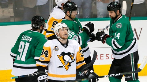 Pittsburgh Penguins' Tom Kuhnhackl (34) of Germany skates away as Dallas Stars' Tyler Seguin (91), Jason Spezza, center rear, and Jamie Benn (14) celebrate a goal by Spezza in the third period of an NHL hockey game, Tuesday, Feb. 28, 2017, in Dallas. (AP Photo/Tony Gutierrez)