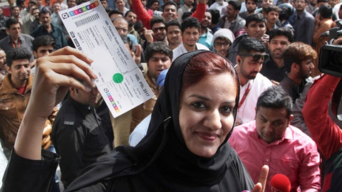 A woman shows ticket for upcoming final cricket match of Pakistan Super League while others gather outside a bank to buy tickets in Lahore, Pakistan, Wednesday, March 01, 2017. Cricket starved people in Pakistan are least worried about which foreign cricketer is coming to Lahore for Sunday's Pakistan Super League final due to security fears. They simply want to know from where they could buy a ticket and witness the final at the Gaddafi Stadium. (AP Photo/K.M. Chaudary)