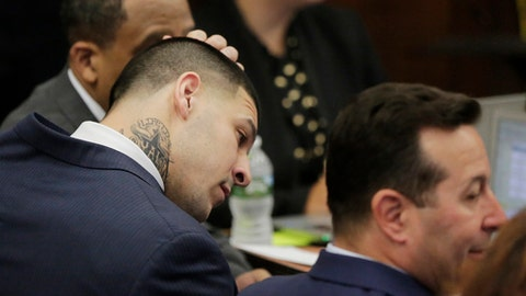 Former New England Patriots tight end Aaron Hernandez rubs his head as he sits with his attorneys on the fist day of his double murder trial at Suffolk Superior Court on Wednesday, March 1, 2017, in Boston. Hernandez is standing trial for the July 2012 killings of Daniel de Abreu and Safiro Furtado who he encountered in a Boston nightclub. He is already serving a life sentence in the 2013 killing of semi-professional football player Odin Lloyd. (AP Photo/Stephan Savoia, Pool)