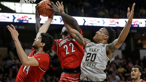 Wake Forest's John Collins (20) competes against Louisville's Deng Adel (22) and Anas Mahmoud (14) for a rebound during the first half of an NCAA college basketball game in Winston-Salem, N.C., Wednesday, March 1, 2017. (AP Photo/Chuck Burton)
