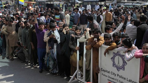 Pakistani cricket lovers gather outside a bank to buy tickets for upcoming final cricket match of Pakistan Super League, in Lahore, Pakistan, Thursday, March 02, 2017. It is supposed to be just a domestic Twenty20 final. But for the Pakistan Cricket Board it's a challenge to showcase the world that it's safe to play international sports in Pakistan. With just three days to go before Sunday's Pakistan Super League finale at the Gaddafi Stadium, still nobody is sure which eight foreign players will put aside their security fears and will eventually play the marque match at the Gaddafi Stadium. (AP Photo/K.M. Chaudary)