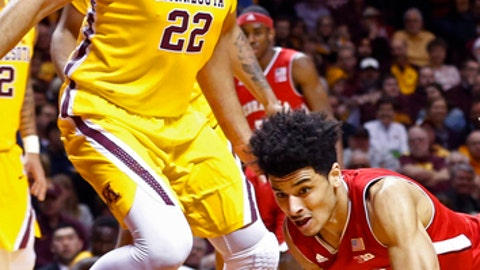Nebraska's Tai Webster, right, of New Zealand, keeps dribbling as he falls under the eyes of Minnesota's Reggie Lynch (22) during the first half of an NCAA college basketball game Thursday, March 2, 2017, in Minneapolis. (AP Photo/Jim Mone)
