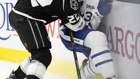 Los Angeles Kings center Trevor Lewis, left, puts Toronto Maple Leafs defenseman Alexey Marchenko, of Russia, into the boards during the second period of an NHL hockey game, Thursday, March 2, 2017, in Los Angeles. (AP Photo/Mark J. Terrill)