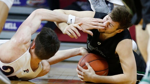 Dartmouth's Taylor Johnson, right, is poked in the face by Penn's A.J. Brodeur during a scramble for the ball in the first half of an NCAA college basketball game Friday, March 3, 2017, in Philadelphia. (Charles Fox/The Philadelphia Inquirer via AP)