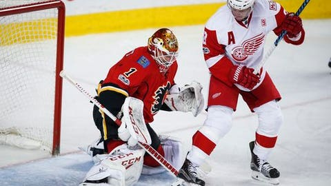 Detroit Red Wings' Justin Abdelkader, right, tries to get the puck past Calgary Flames goalie Brian Elliott during second-period NHL hockey gam action in Calgary, Alberta, Friday, March 3, 2017. (Jeff McIntosh/The Canadian Press via AP)