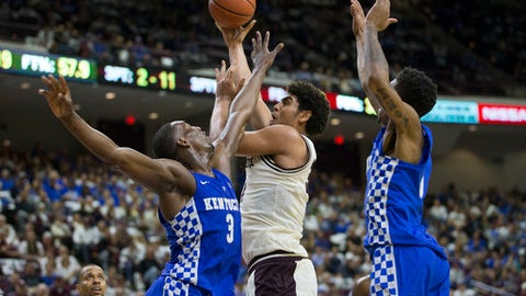 Texas A&M center Tyler Davis (34) shoots around Kentucky's Edrice Adebayo (3) and Malik Monk (5) during an NCAA college basketball game, Saturday, March 4, 2017, in College Station, Texas. (AP Photo/Sam Craft)