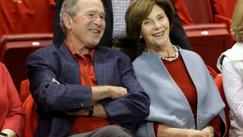 Former President George W. Bush, left, sits with his wife Laura Bush before an NCAA college basketball game between SMU and Memphis Saturday, March 4, 2017, in Dallas. (AP Photo/LM Otero)
