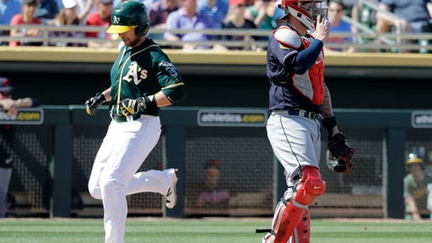 Oakland Athletics' Jed Lowrie scores as Cleveland Indians catcher Roberto Perez watches during the first inning of a spring training baseball game Saturday, March 4, 2017, in Mesa, Ariz. (AP Photo/Darron Cummings)