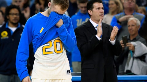 UCLA guard Bryce Alford, left, wipes his eyes after being introduced as an outgoing senior as his father, UCLA coach Steve Alford, applauds prior to the team's NCAA college basketball game against Washington State, Saturday, March 4, 2017, in Los Angeles. (AP Photo/Mark J. Terrill)