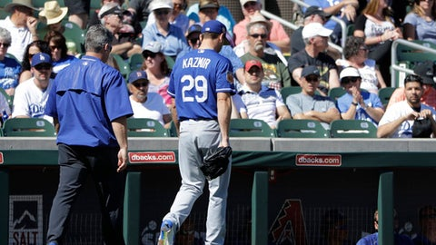 Los Angeles Dodgers' Scott Kazmir leaves with a trainer during the second inning of a spring training baseball game against the Colorado Rockies, Monday, March 6, 2017, in Scottsdale, Ariz. (AP Photo/Darron Cummings)