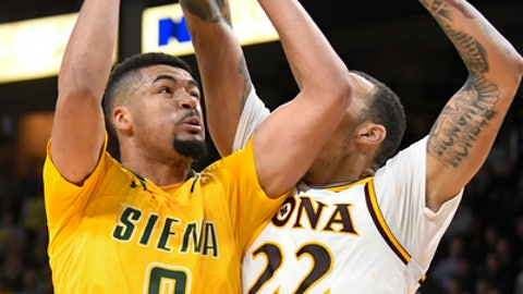 Siena forward Javion Ogunyemi (0) moves the ball against Iona forward Taylor Bessick (22) during the first half of an NCAA college basketball game in the championship of the Metro Atlantic Athletic Conference tournament on Monday, March 6, 2017, in Albany, N.Y. (AP Photo/Hans Pennink)