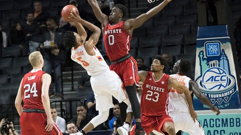 Clemson forward Jaron Blossomgame (5) goes to the basket as North Carolina State forward Abdul-Malik Abu (0) defends during the first half an NCAA college basketball game in the Atlantic Coast Conference tournament, March 7, 2017, in New York. (AP Photo/Mary Altaffer)