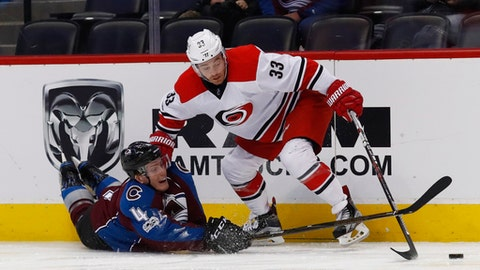 Colorado Avalanche defenseman Tyson Barrie, left, fights for control of the puck with Carolina Hurricanes center Derek Ryan in the second period of an NHL hockey game Tuesday, March 7, 2017, in Denver. (AP Photo/David Zalubowski)