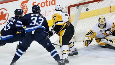 Winnipeg Jets' Dustin Byfuglien (33) scores on Pittsburgh Penguins goalie Matt Murray (30) as Matt Cullen (7) defends and Jets' Mathieu Perreault (85) watches during the first period of an NHL hockey game Wednesday, March 8, 2017, in Winnipeg, Manitoba. (John Woods/The Canadian Press via AP)