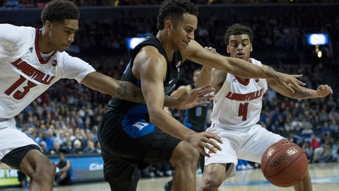Duke guard Frank Jackson, center, vies for a loose ball against Louisville forward Ray Spalding (13) and guard Quentin Snider (4) during the first half of an NCAA college basketball game in the Atlantic Coast Conference tournament, Thursday, March 9, 2017, in New York. (AP Photo/Mary Altaffer)