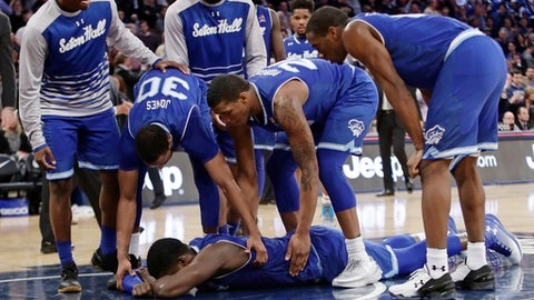 Seton Hall's Angel Delgado, bottom, is consoled by teammates after an NCAA college basketball game against Villanova during the Big East men's tournament Friday, March 10, 2017, in New York. Villanova won 55-53. (AP Photo/Frank Franklin II)