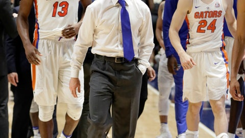 Florida head coach Mike White leaves the court with Kevarrius Hayes (13) and Canyon Barry (24) after Florida was upset by Vanderbilt 72-62 in overtime in an NCAA college basketball game at the Southeastern Conference tournament Friday, March 10, 2017, in Nashville, Tenn. (AP Photo/Mark Humphrey)