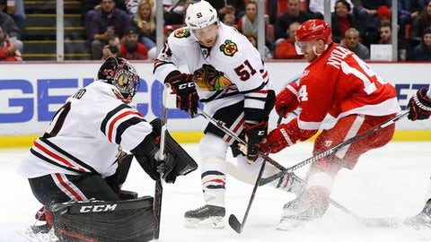 Chicago Blackhawks defenseman Brian Campbell (51) defends Detroit Red Wings right wing Gustav Nyquist (14) as goalie Corey Crawford, left, blocks a shot in the second period of an NHL hockey game Friday, March 10, 2017, in Detroit. (AP Photo/Paul Sancya)