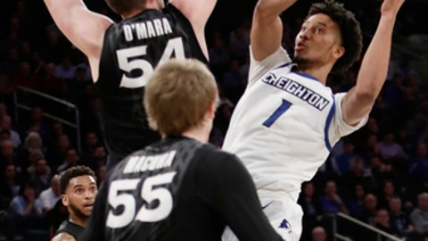 Creighton's Davion Mintz (1) shoots over Xavier's Sean O'Mara (54) and J.P. Macura (55) during the first half of an NCAA college basketball game during the Big East men's tournament Friday, March 10, 2017, in New York. (AP Photo/Frank Franklin II)