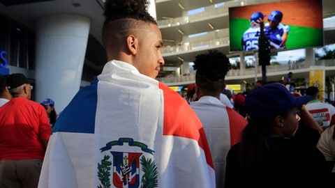 A fan is draped with the flag of the Dominican Republic outside Marlins Park before a first-round game of the World Baseball Classic between the U.S. and the Dominican Republic, Saturday, March 11, 2017, in Miami. (AP Photo/Lynne Sladky)