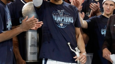 Villanova's Josh Hart, center, gestures to the crowd while holding the Most Outstanding Player trophy and posing for photographs with his teammates after a championship NCAA college basketball game against Creighton in the finals of the Big East men's tournament Saturday, March 11, 2017, in New York. Villanova won 74-60. (AP Photo/Frank Franklin II)