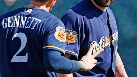 Milwaukee Brewers second baseman Scooter Gennett (2) holds up two fingers to see how well pitcher Joba Chamberlain, right, can see after Chamberlain lost an infield high hop ground ball hit by Cincinnati Reds'  Stuart Turner in the sun for an infield hit during the fourth inning of a spring training baseball game Sunday, March 12, 2017, in Goodyear, Ariz. (AP Photo/Ross D. Franklin)