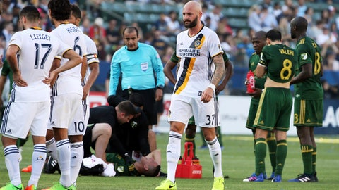 LA Galaxy defender Jelle Van Damme (37) walks off the field after receiving a red card as Portland Timbers midfielder David Guzman (20) is treated on the field in the first half of an MLS soccer game in Carson, Calif., Sunday, March 12, 2017. (AP Photo/Reed Saxon)