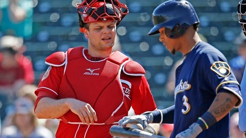 Cincinnati Reds catcher Devin Mesoraco, left, talks with Brewers shortstop Orlando Arcia (3) at home plate during the first inning of a spring training baseball game Sunday, March 12, 2017, in Goodyear, Ariz. The Reds defeated the Brewers 4-2. (AP Photo/Ross D. Franklin)