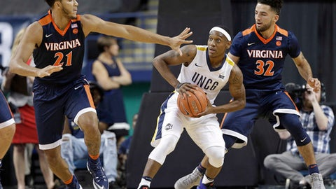 "FILE - In this Nov. 11, 2016, file photo, UNC-Greensboro's Diante Baldwin, center, is trapped by Virginia's Isaiah Wilkins, left, and London Perrantes, right, in the first half of an NCAA college basketball game in Greensboro, N.C. Four days after Syracuse head coach Jim Boeheim angered an entire city by saying there was ""no value"" in the Atlantic Coast Conference holding its postseason tournament in Greensboro, N.C., the Orange were matched up on Sunday, March 12, 2017, against UNC Greensboro in the first round of the National Invitation Tournament. (AP Photo/Chuck Burton, File)"