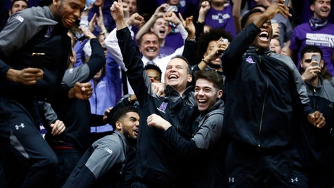 Northwestern coach Chris Collins, center, and players react while watching the broadcast of the NCAA men's basketball tournament selection show, Sunday, March 12, 2017, in Evanston, Ill. Northwestern will play Vanderbilt in the first round, in Northwestern's first appearance in the tournament. (AP Photo/Nam Y. Huh)