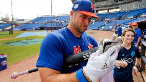 New York Mets' Tim Tebow helps a fan take a photograph before a spring training baseball game against the Miami Marlins, Monday, March 13, 2017, in Port St. Lucie, Fla. (AP Photo/John Bazemore)