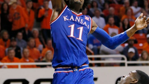 FILE - In this March 4, 2017, file photo, Kansas guard Josh Jackson (11) dunks in front of Oklahoma State guard Jawun Evans, right, in the second half of an NCAA college basketball game in Stillwater, Okla. Kansas coach Bill Self says star freshman Josh Jackson will play in the NCAA Tournament despite several off-the-court issues and allegations that Jackson and his representatives tried to bribe a student to make a vandalism accusation go away. (AP Photo/Sue Ogrocki, File)