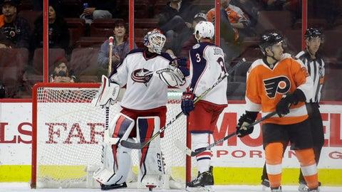 Columbus Blue Jackets' Sergei Bobrovsky, left, and Seth Jones, center, celebrate as Philadelphia Flyers' Matt Read skates off after the Blue Jackets won an NHL hockey game, 5-3, Monday, March 13, 2017, in Philadelphia. (AP Photo/Matt Slocum)