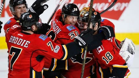 Calgary Flames left wing Matthew Tkachuk (19), from left, defenseman TJ Brodie (7), right wing Alex Chiasson (39), goalie Brian Elliott (1) and center Matt Stajan (18) celebrate their shootout win during overtime of an NHL hockey game against the Pittsburgh Penguins in Calgary, Alberta, Monday, March 13, 2017. (Jeff McIntosh/The Canadian Press via AP)