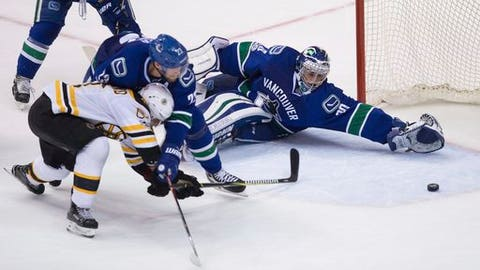 Boston Bruins left wing Brad Marchand (63) scores against Vancouver Canucks goalie Ryan Miller (30) while being checked by defenseman Alexander Edler (23), of Sweden, during the third period of an NHL hockey game in Vancouver, British Columbia, Monday, March 13, 2017. (Darryl Dyck/The Canadian Press via AP)