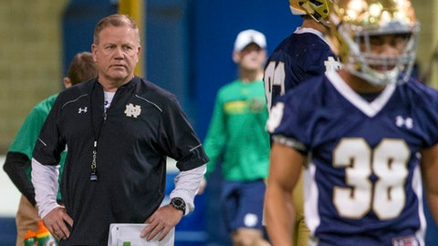 FILE - In this Wednesday, March 8, 2017, file photo, Notre Dame head coach Brian Kelly, left, runs drills during spring NCAA college football practice at the Loftus Sports Center in South Bend, Ind. Kelly is doing some things differently this spring. He feels he has to after a 4-8 season that in many ways was a disaster for the Fighting Irish. (Becky Malewitz/South Bend Tribune via AP, File)