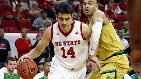 North Carolina State 's Omer Yurtseven (14) drives the ball around Notre Dame's Austin Torres (1) during the first half of an NCAA college basketball game in Raleigh, N.C., Saturday, Feb. 18, 2017. (AP Photo/Karl B DeBlaker)