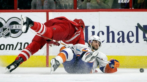 New York Islanders' Stephen Gionta, right, and Carolina Hurricanes' Jaccob Slavin chase the puck during the second period of an NHL hockey game in Raleigh, N.C., Tuesday, March 14, 2017. (AP Photo/Gerry Broome)