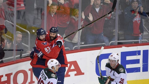 Washington Capitals center Jay Beagle (83) celebrates his goal with left wing Daniel Winnik (26) as Minnesota Wild defenseman Jared Spurgeon (46) and defenseman Ryan Suter (20) skate by during the third period of an NHL hockey game, Tuesday, March 14, 2017, in Washington. The Capitals won 4-2. (AP Photo/Nick Wass)